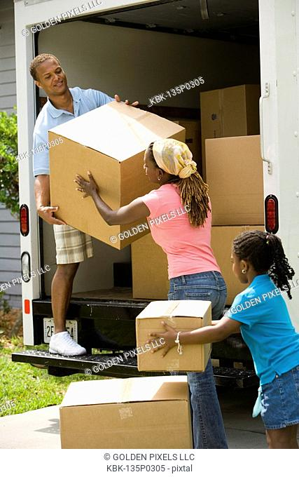 Family unloading boxes from a moving truck