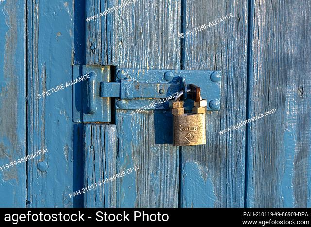 17 January 2021, Saxony-Anhalt, Wolmirstedt: A golden padlock hangs on a blue wooden door. It is secured with four nuts so that it cannot be picked easily by...
