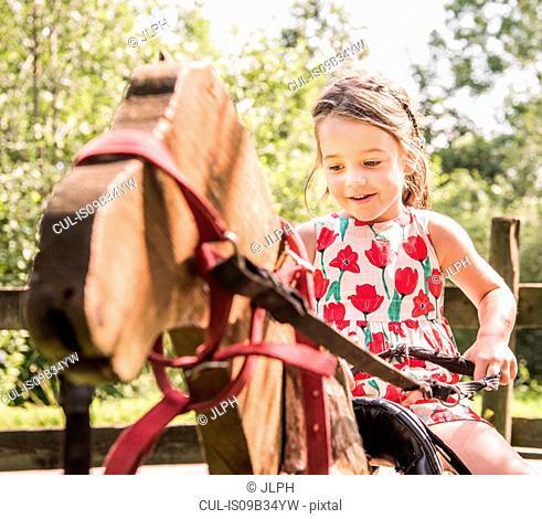 Girl on wooden hobby horse smiling