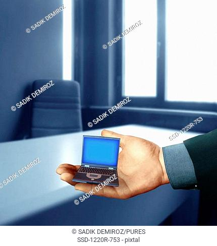 Person's hand holding a miniature laptop