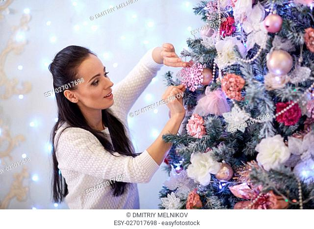 Beautiful young woman is decorating a Christmas tree in the house. Merry Christmas and New Year