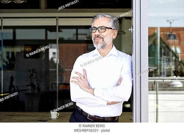 Smiling businessman standing at French door thinking
