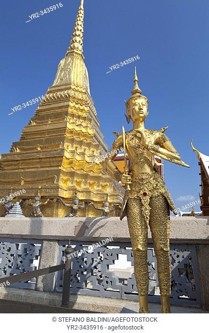 Statue of Kinnon, male counterpart of a Kinnaree (Kinaree or Ginnaree) at Wat Phra Kaeo with a golden chedi behind, the Royal Grand Palace, Bangkok, Thailand