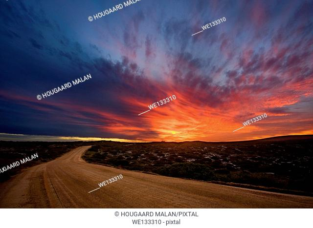 Landscape photo of a colourful sunset over a road in the West Coast National Park. Langebaan, South Africa