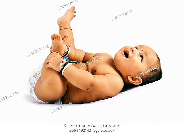 Cute baby sleeping on bed holding his feet and laughing, Pune, Maharashtra