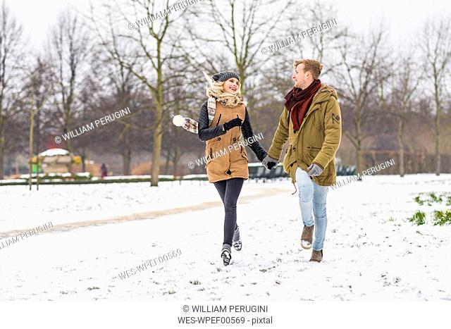 Happy young couple in love walking hand in hand in a park on snowy day