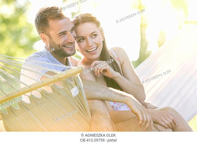Affectionate young couple smiling in summer hammock