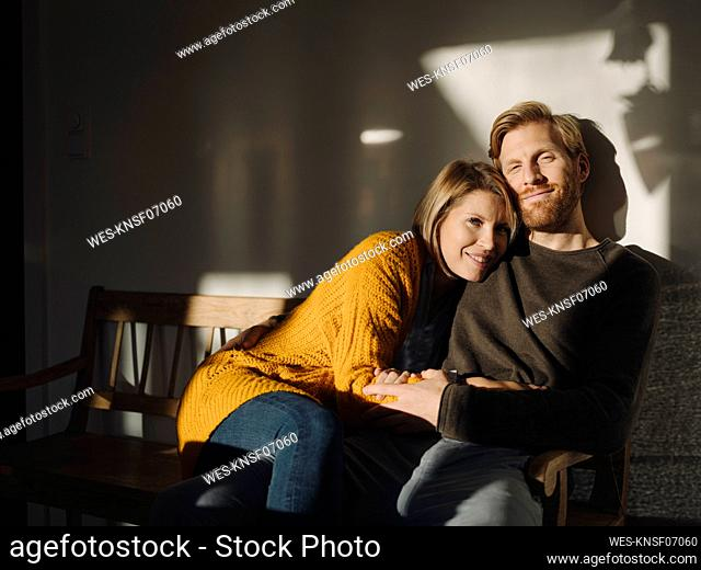 Portrait of smiling couple sitting on bench in sunlight at home