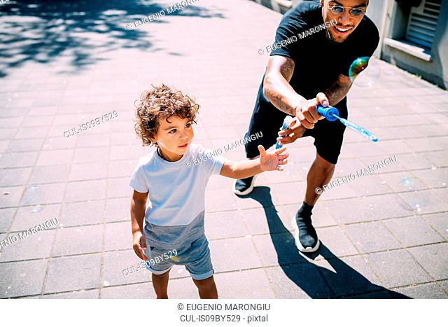 Father and son playing with soap bubbles on sidewalk