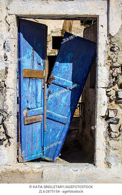 Blue broken wooded door of houses situated in Pyros the quaint medieval village in Santorini island, Cyclades, Greece