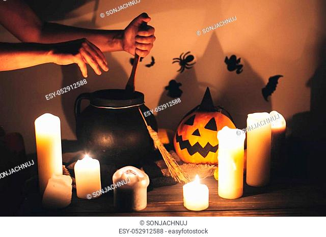 witch hand boiling potion for spell, with jack o lantern pumpkin with candles, broom and bats, ghosts on background in dark spooky room
