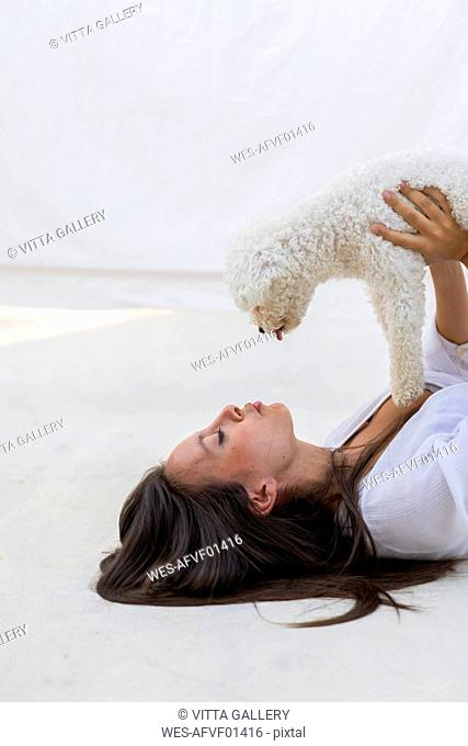 Young woman having fun with dog on roof terrace