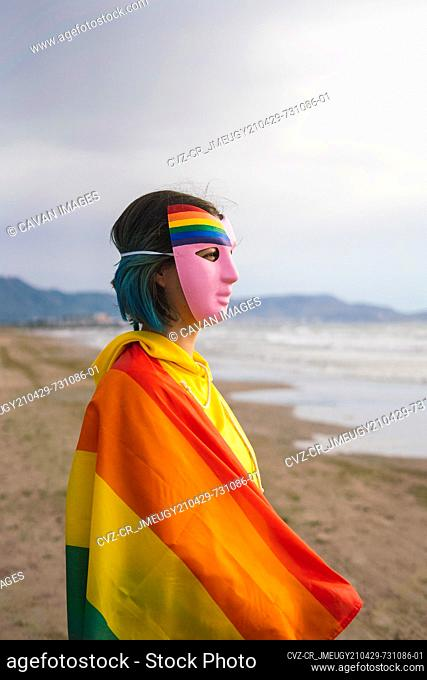 Masked person with pink mask with LGBT rainbow flag on the beach