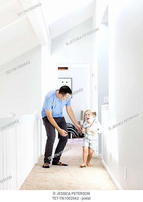 Father and son (4-5) playing in corridor