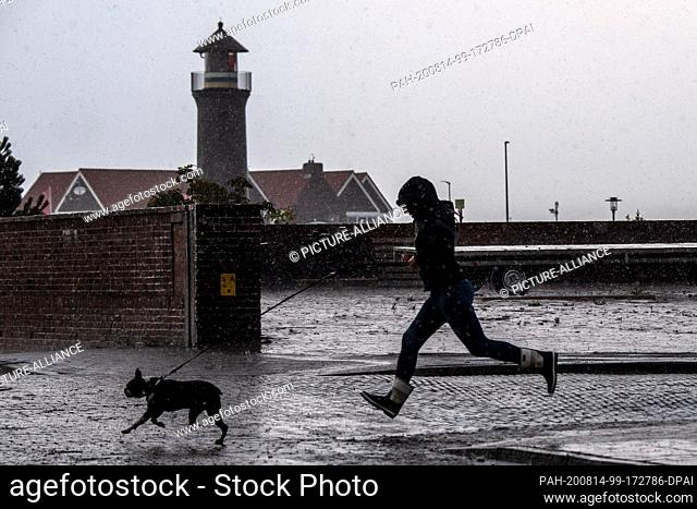 14 August 2020, Lower Saxony, Juist: A woman in rubber boots runs with her dog in the pouring rain past the lighthouse Memmertfeuer