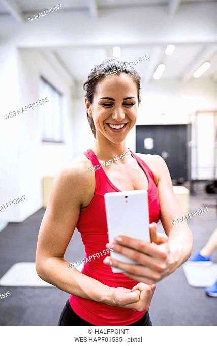 Young female athete taking selfies in gym