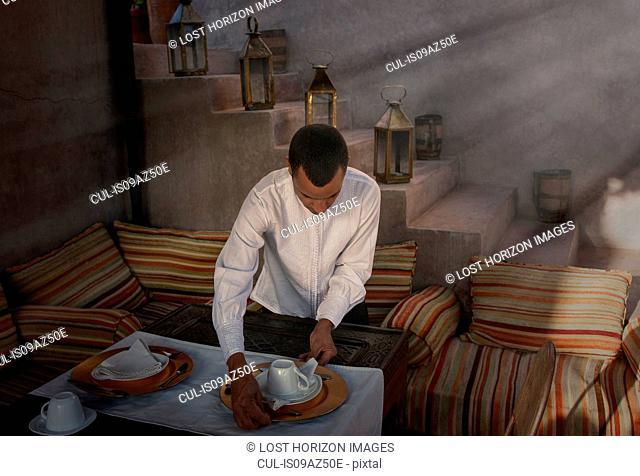 Waiter preparing place settings, Marrakesh, Morocco
