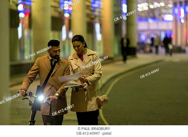 Business people with bicycle and paperwork walking on urban street at night
