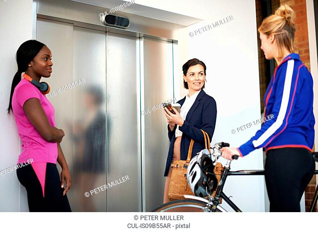 Female colleagues waiting for office lift
