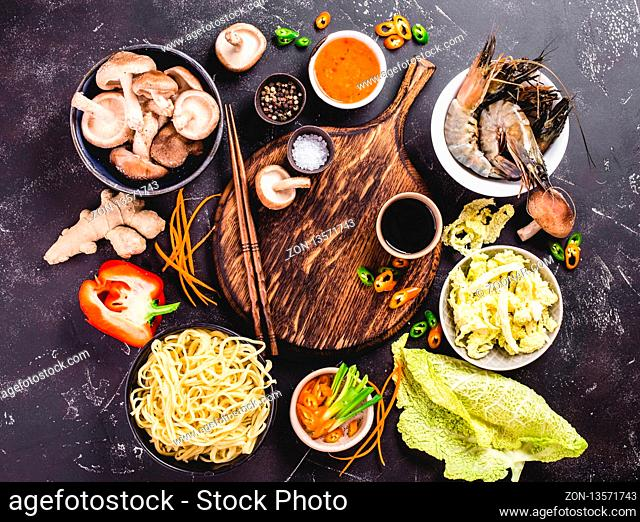 Asian food cooking concept. Empty wooden board, noodles, vegetables stir fry, shrimps, sauces, chopsticks. Asian/Chinese food. Top view
