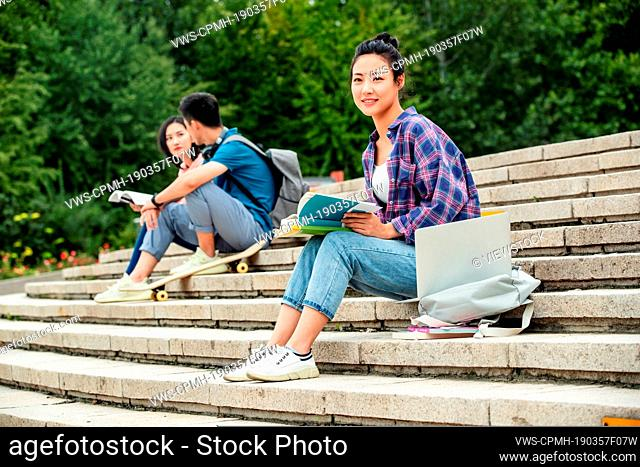Happy college students sat on the steps of learning
