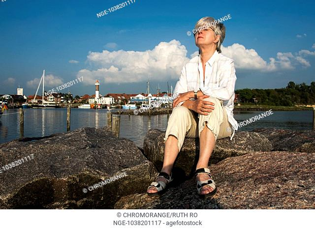 a woman sitting on the pier in the harbor Timmendorf