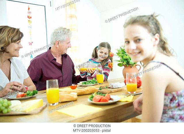 Grandparents and granddaughters sitting at table in living room, smiling