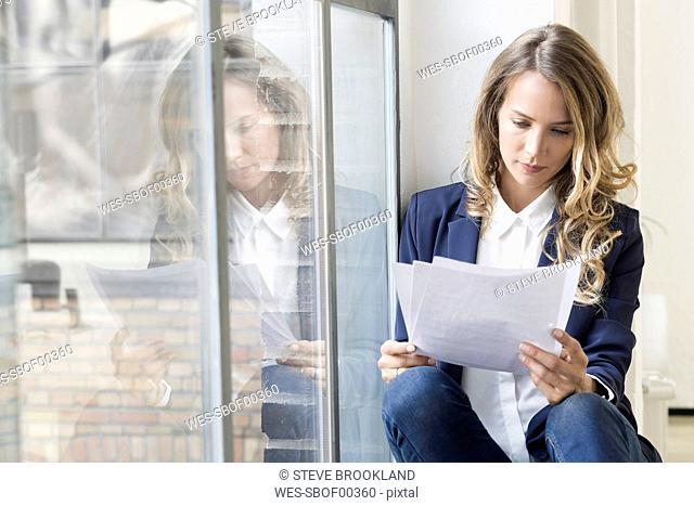 Businesswoman sitting in her office, reading papers