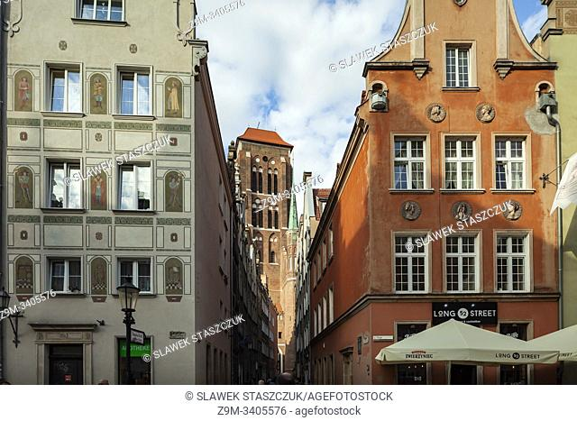 Narrow street in Gdansk old town, Poland. St Mary's basilica tower in the distance