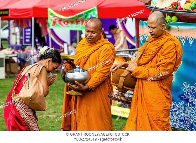 Thai People Offer Food To Two Monks At The Brighton Thai Festival, Preston Park, Brighton, Sussex, UK