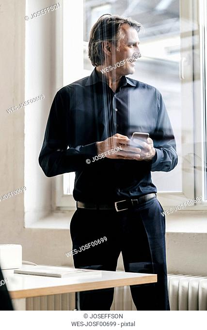 Smiling mature businessman holding cell phone at the window
