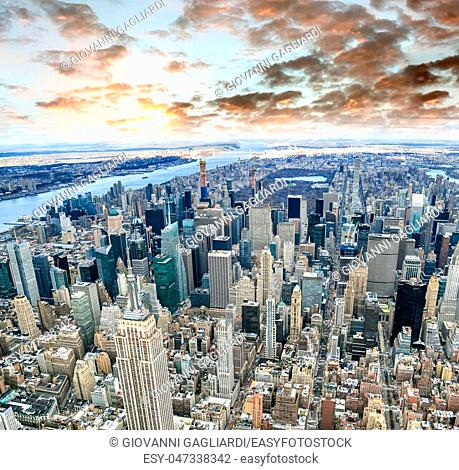 Aerial view of Manhattan skyline from the sky on a cloudy day, New York City at sunset