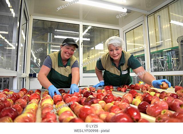 Female workers checking apples on conveyor belt in apple-juice factory