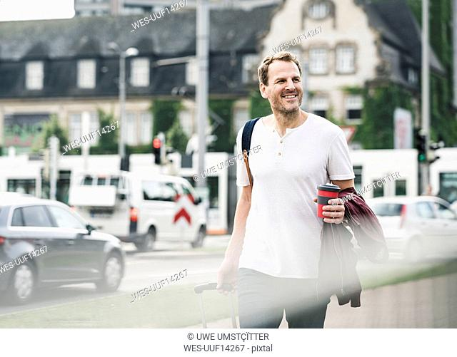 Smiling man with rolling suitcase and takeaway coffee walking in the city