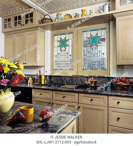 KITCHENS - View towards cooking stove top, granite counter tops, stained glass windows over stove top, wood cabinets with pane glass doors