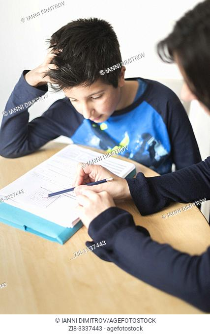 Private tutoring at home-10-11 years boy having a maths lesson at home