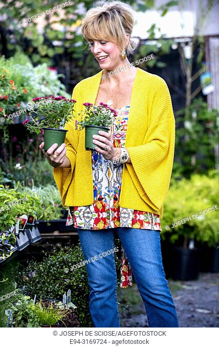 A pretty 42 year old blond woman shopping at a garden store