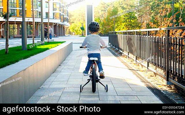 Rear view photo of little toddler boy riding bicycle for first time on pathway