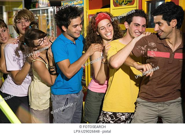 Teenagers pushing on line in arcade