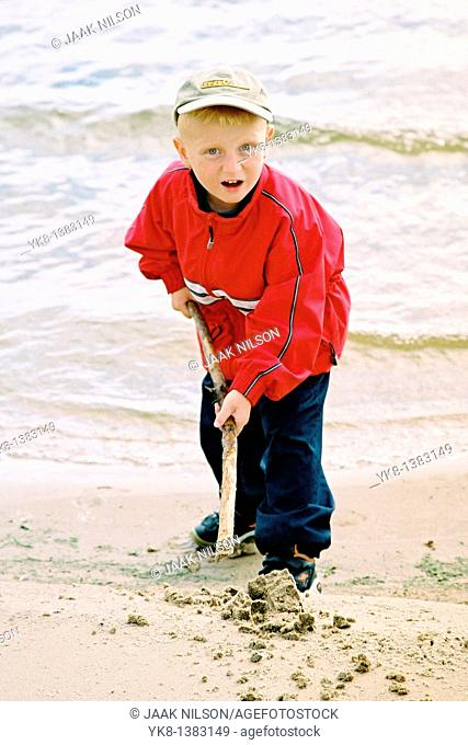 Five Year Old Boy Playing with Wooden Stick on Beach By Water