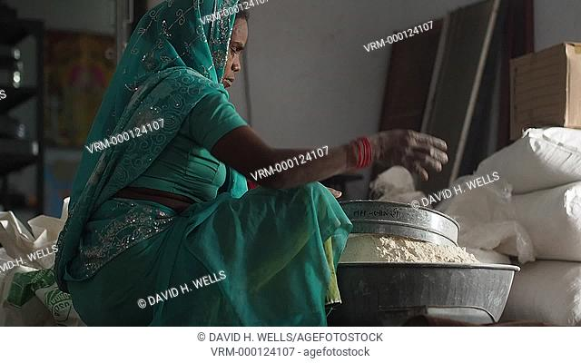 Mature woman straining grains on a farm in Ahmedabad, Gujarat, India