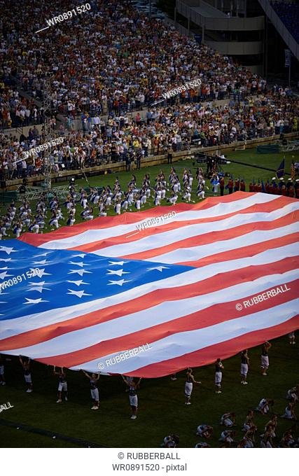 High angle view of a group of people holding a large American Flag