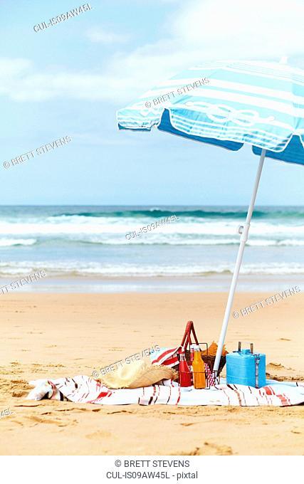 Sunhat, cool box and picnic basket on beach towel underneath parasol on beach