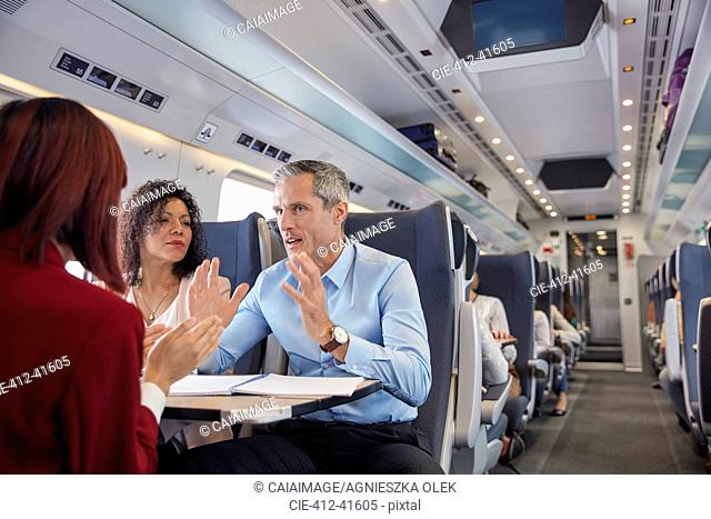 Business people working, talking on passenger train