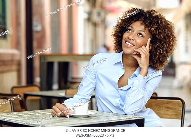 Smiling woman with afro hairstyle sitting in outdoor cafe