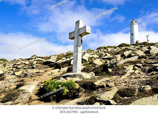 Cross for a victim of a shipwreck and the lighthouse of Laxe - death coast, Galicia Spain
