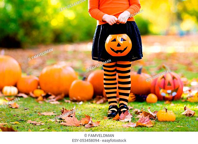 Kids with pumpkin on Halloween. Little girl in witch costume and hat playing in autumn park. Child at Halloween trick or treat. Kid trick or treating
