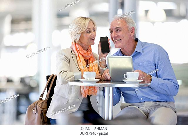 Smiling couple talking on cell phone and using digital tablet at cafe table