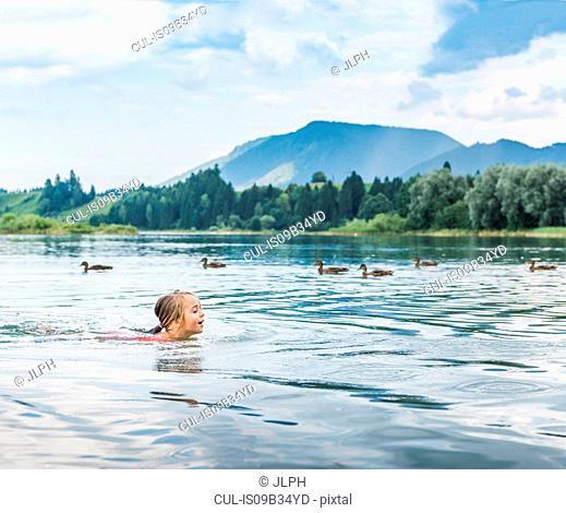 Girl swimming in lake, Fuessen, Bavaria, Germany