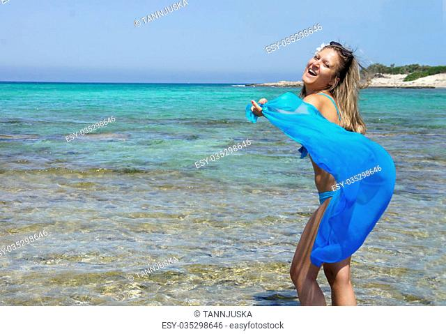 Young happy woman on the beach with blue shawl